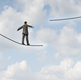 pic of dangerous situation  - Difficult situation business concept with a businessman walking on a tightrope or high wire metaphor that has been cut and moved higher resulting in increased risk and danger to a planned strategy - JPG