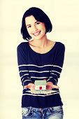 Beautiful young woman holding US dollars bills and house model  - real estate loan concept
