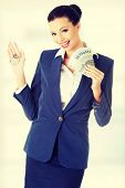 Beautiful young woman holding euro and house keys- real estate loan concept