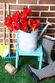 Composition of colorful tulips in watering can and rain boots on bright background