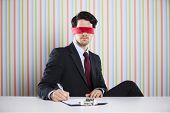 Blindfold businessman at his office signing contracts
