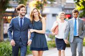 Young Business Couples Walking Through City Park Together
