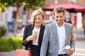 Business Couple Walking Through Park With Takeaway Coffee