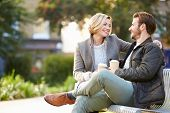 image of takeaway  - Couple Relaxing On Park Bench With Takeaway Coffee - JPG