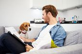 Man Looking At Paperwork And Playing With Pet Dog At Home