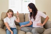 pic of stubborn  - Stubborn girl showing stop gesture to mother while sitting on sofa at home - JPG