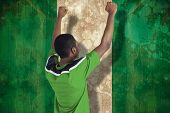 Cheering football fan in green jersey against nigeria flag in grunge effect