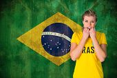 Nervous football fan in brasil tshirt against brazil flag in grunge effect