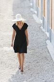 Beautiful blonde girl young woman walking in white hat and little black dress
