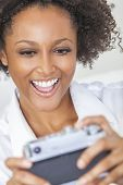 A beautiful mixed race African American girl or young woman laughing and taking a selfie picture on