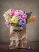 Hyacinths and ranunculus flowers in a bag