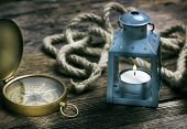 Compass and lantern on old wooden table