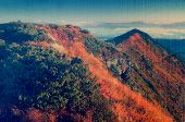 Warm sunlight on the mountain slopes. Morning landscape with mountain peaks. Dry autumn grass in the