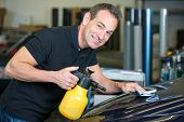 image of cleaning agents  - Worker cleaning car with cloth and spray bottle in garage or workshop