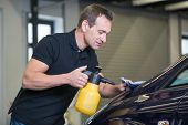stock photo of cleaning agents  - Worker cleaning car with cloth and spray bottle in garage or workshop