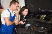 Mechanics In Garage Inspecting Car For Damages