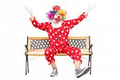 Clown gesturing happiness seated on bench isolated on white background