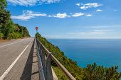Empty asphalt road and beautiful view on Mediterranean sea from above under blue sky in Liguria, Italy.
