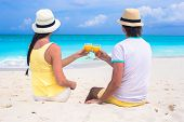 Happy couple with two glasses of orange juice on a tropical beach