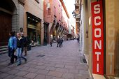 BOLOGNA, ITALY - APRIL 19, 2014:  Pedestrians walk past a sign announcing a store wide sale in Bologna, Italy, on Saturday, April 19, 2014.