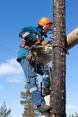 Electrician Working On Electricity Pylon Chainsaw