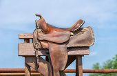 foto of reining  - Leather horse saddle displayed on a stand against blue sky - JPG