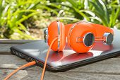 Bright Coloured Orange Headphones And Mobile Computer