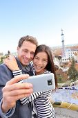 Happy travel couple talking selfie self-portrait with smartphone in Park Guell, Barcelona, Spain. Be