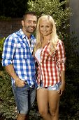 Portrait of happy married couple outdoors, with attractive blonde, smiling woman and stubbly handsome man, wearing checkered shirt, shorts, looking at camera.