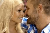 Close up of happy romantic young couple outdoor. Attractive blonde, smiling woman and stubbly handsome man.
