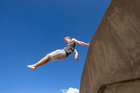 foto of parkour  - Teen boy jumping off wall somersault in blue sky in parkour on beach - JPG