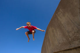 picture of parkour  - Teen boy jumping off wall in blue sky in parkour on beach - JPG