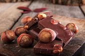 A Stack Of Chocolate With Hazelnuts On Wooden Table
