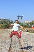 Male Teenager Jumps In Retro Park And Wearing Sunglasses