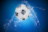 Water splash with sport ball on blue background