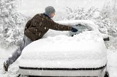stock photo of cold-weather  - Young man brushing the snow off his car on a cold winter day in snowfall - JPG