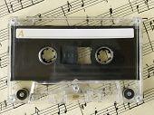 Cassette on old sheet music, closeup