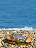 Mobile phone on beach, sea on background