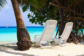 Chairs on tropical beach, abstract vacation background