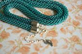 Necklace Of Color Aquamarine From Beads Against A Flower Print