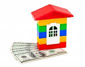 Toy house and money isolated on white background