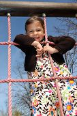 Girl hanging onto a rope ladder