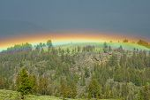 stock photo of lamar  - Rainbow arcs Lamar Valley during a storm - JPG