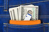 Money and flash memory in jeans pocket - business background