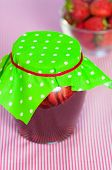 Jar of strawberry jam on  table