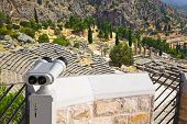Binoculars and ancient city Delphi, Greece - archaeology background