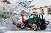 Tractor blower cleaning snow in street - Obergurgl Austria