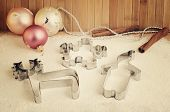 Tinted Image Cookie Cutters And Christmas Tree Decorations On The Table With Flour Horizontal