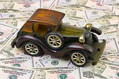 Toy retro car on money background - business concept