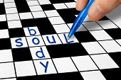 Hand filling in crossword - Soul and Body